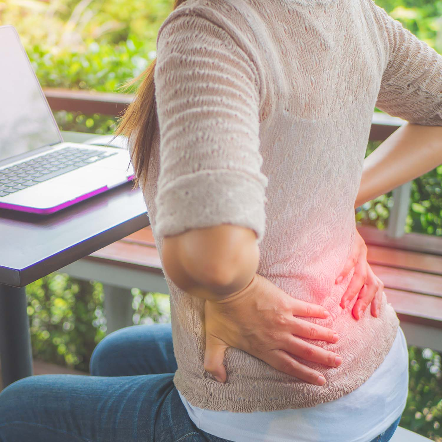 Young woman sitting with back pain
