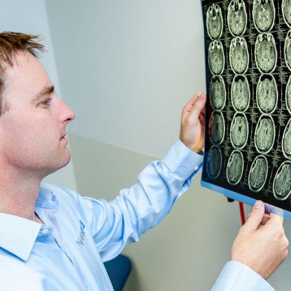 Dr Andrew Gardner examining brain scans