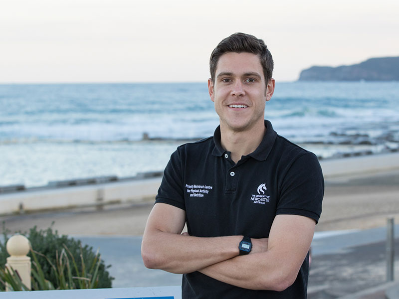Dr Lee Ashton smiling in front of a beach, wearing a University of Newcastle shirt, arms crossed