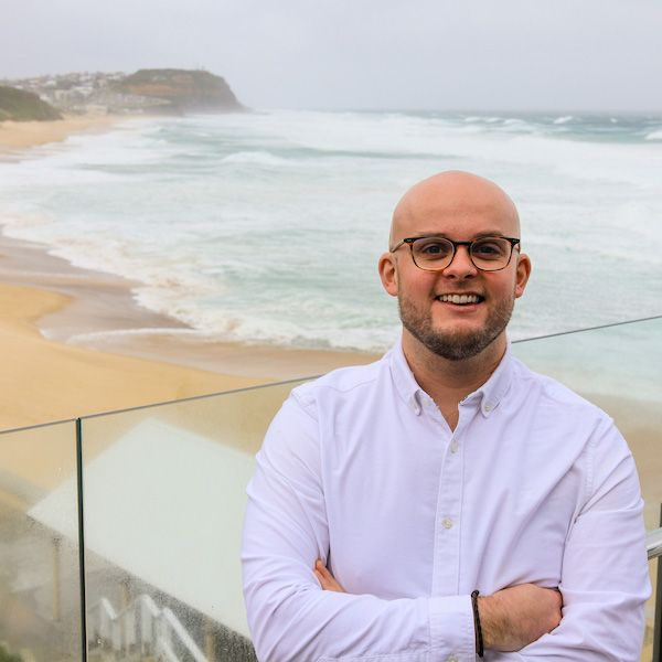 Image of Dr Andrew Magee with beach behind him