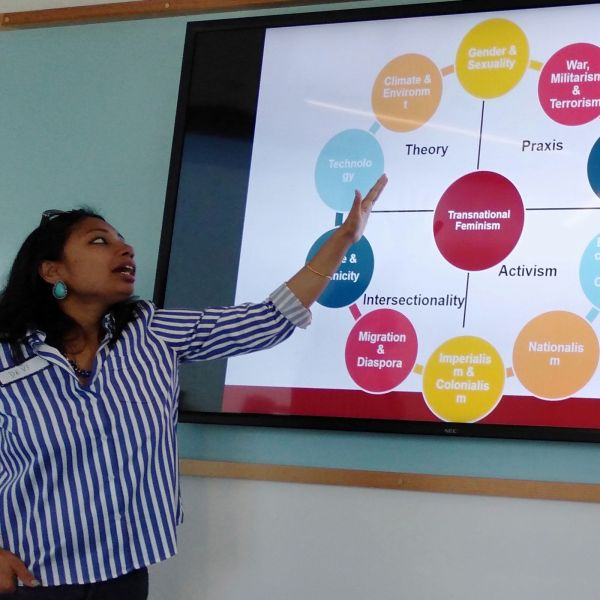 Dr Devaleena Das pointing at a projected chart