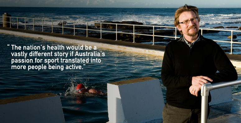 Professor Ron Plotnikoff sitting on a starting block at the ocean baths