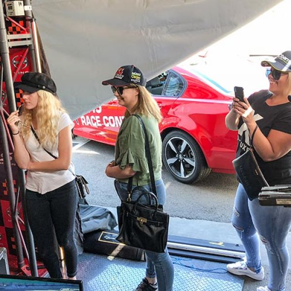 Three female students standing in a Supercar tent with a red car in the background