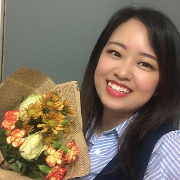Vicki Shi smiling, holding flowers