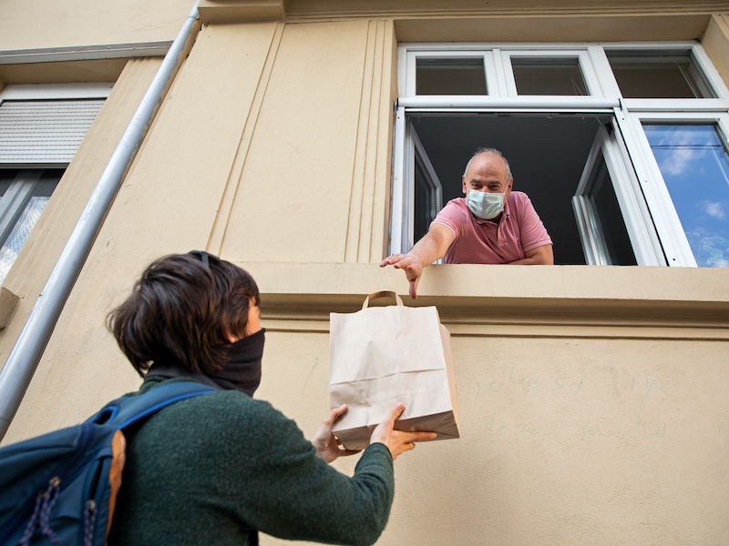 Person handing man groceries through window, wearing medical mask