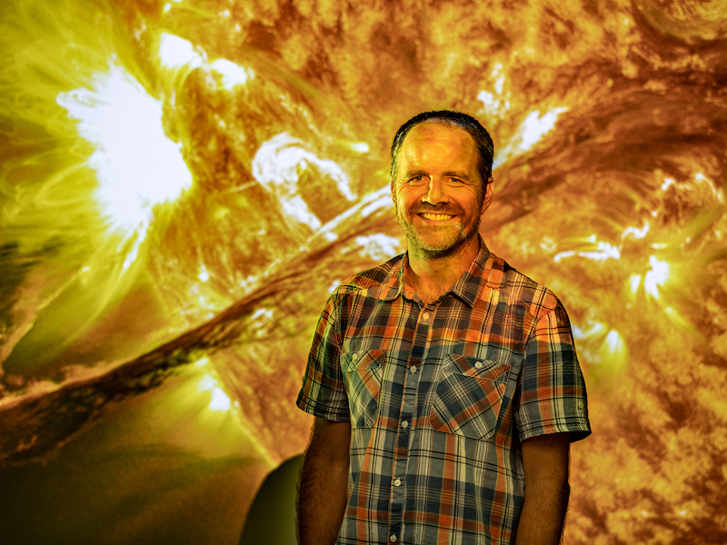 David Pontin standing in front of projection of the sun