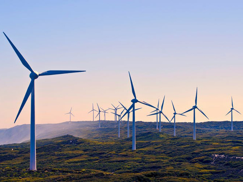 Wide shot featuring wind turbines against hilly terrain and sunset