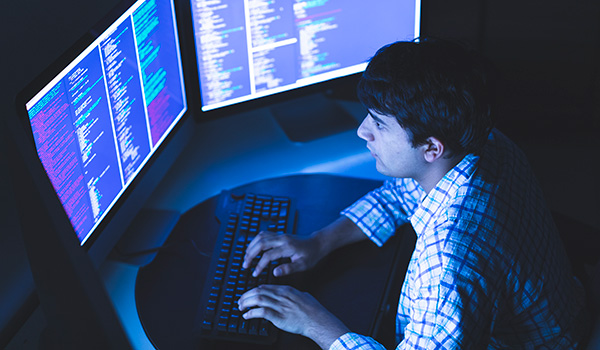 Cyber security student at computer with two monitors