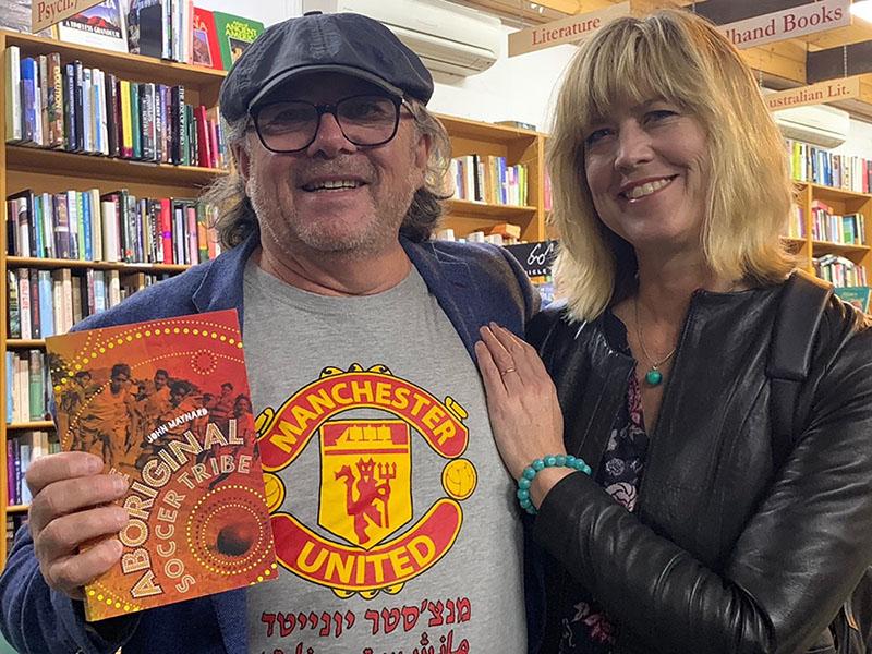 John Maynard and partner, Victoria Haskins smiling in bookshop holding John's book