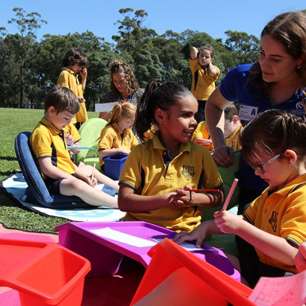 Students writing letters with the help of University Occupational Therapy student Maddie