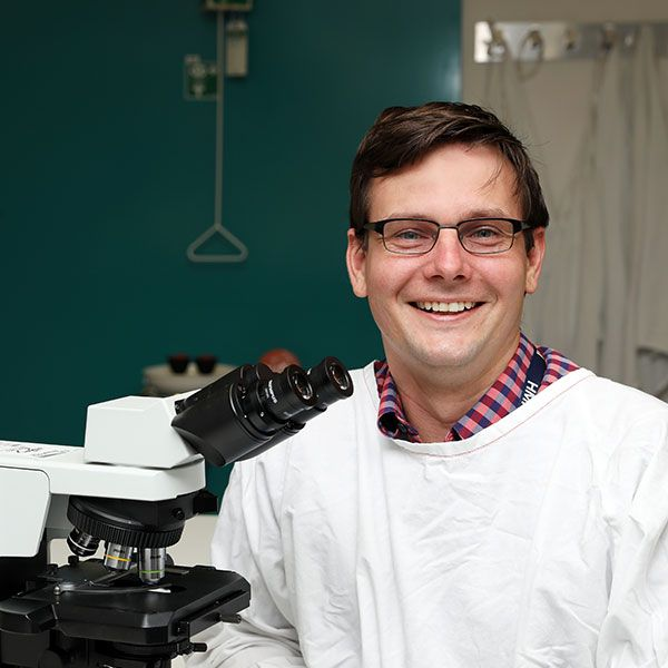 Image of a researcher in front of a microscope smiling at the camera