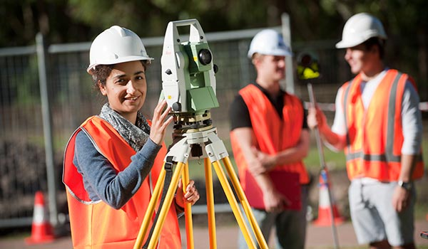 Female student in orange vest and hardhat stands with surveying equipment and two male students stand in background.