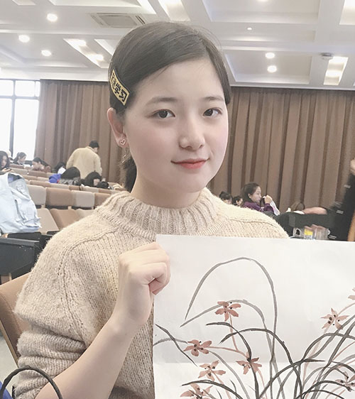 Flora Xu smiling in lecture theatre, holding painting