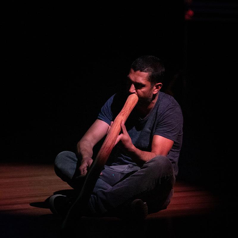 Man sitting on the ground playing the didgeridoo