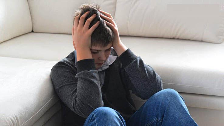 Young boy sitting on floor looking sad
