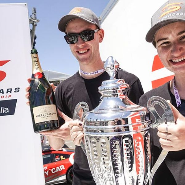 A male and female UON student holding the Supercars trophy