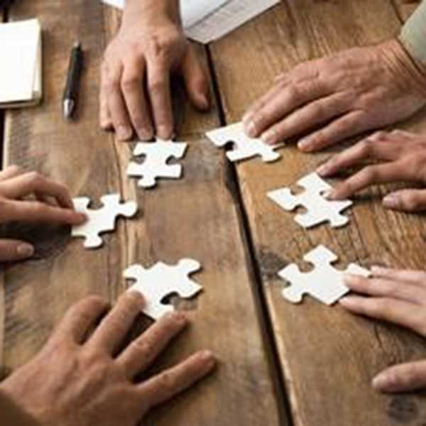 5 hands each holding a puzzle piece trying to fit them together