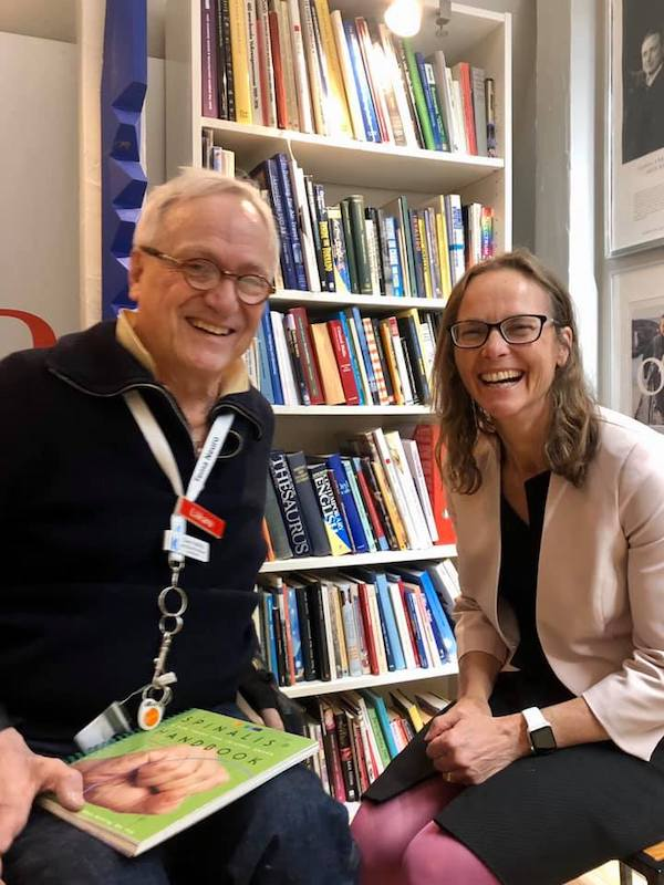 Professor Jennifer Martin smiling with Professor Claes Hultling in front of a book casein Stockholm