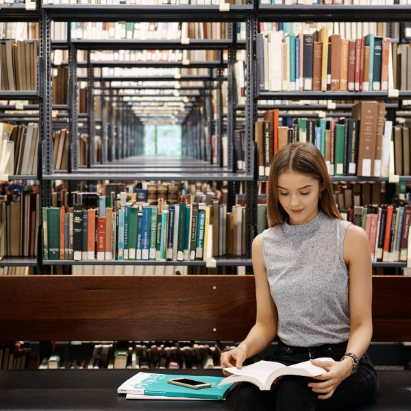 Student reading a book in the library at the University of Newcastle