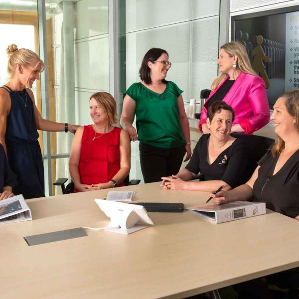 Seven female academics talking around a table