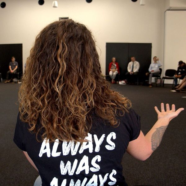 Image of woman addressing group of people with tshirt that says Always Was