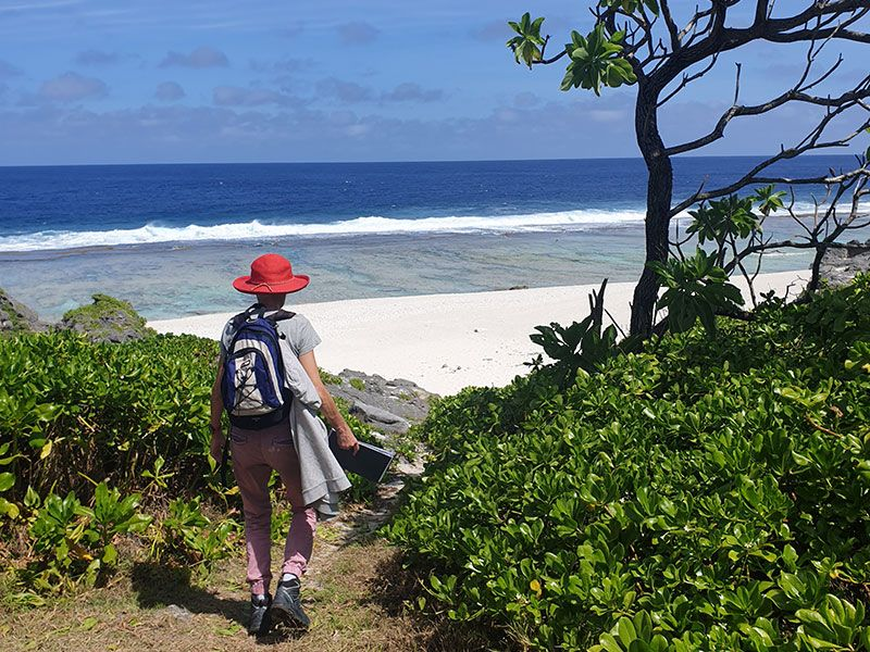 Person with a red hat heading to the beach