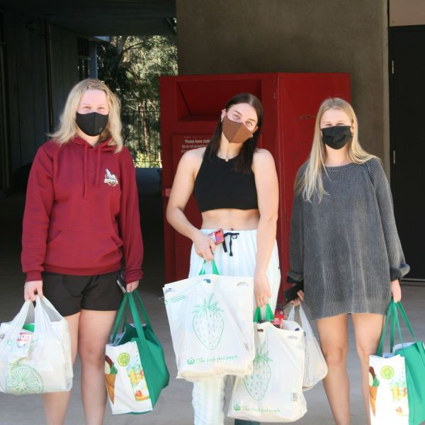 Three students receive their care packages
