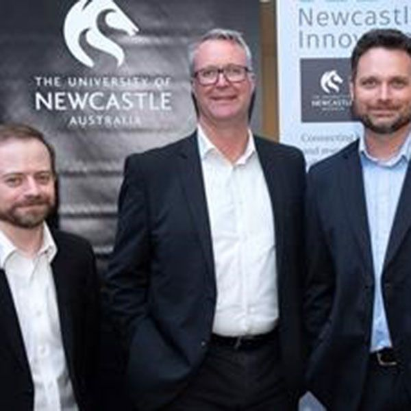 Three men standing in front of a University of Newcastle logo banner