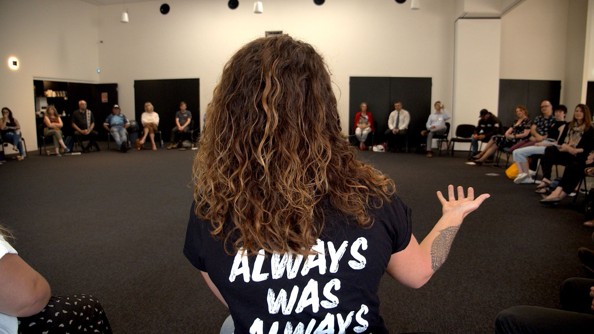 Woman addresses room with shirt that says Always Was