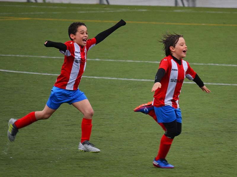 Two kids celebrate scoring a football goal