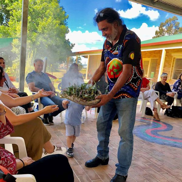 As guests sit around a circle at the launch ceremony of the speech pathology event at Kempsy they are welcomed to be a part of the smoking ceremony