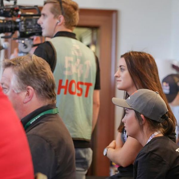 UON students sit and watch a cameraman filming the Supercars race