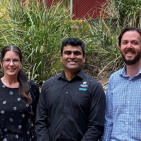 Dr Kim Maud (female, wearing glasses and brown hair in a pony tail), Associate Professor Thayaparan Gajendran (male wearing glasses and dark button-up University of Newcastle shirt)and Mark Maund (male with brown hair, beard wearing blue checkered shirt)smiling in front of bushes