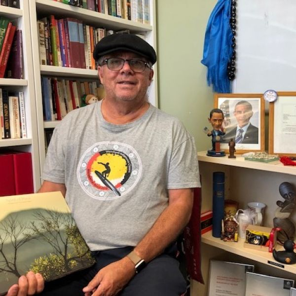 Professor Maynard sitting holding a book in front of a cabinet of memorabilia collected as an historian