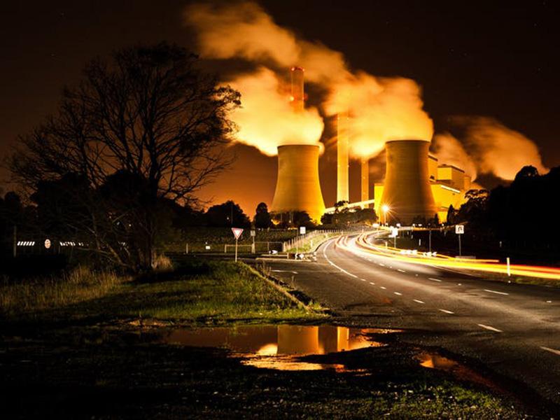 Night shot featuring factory chimneys billowing smoke
