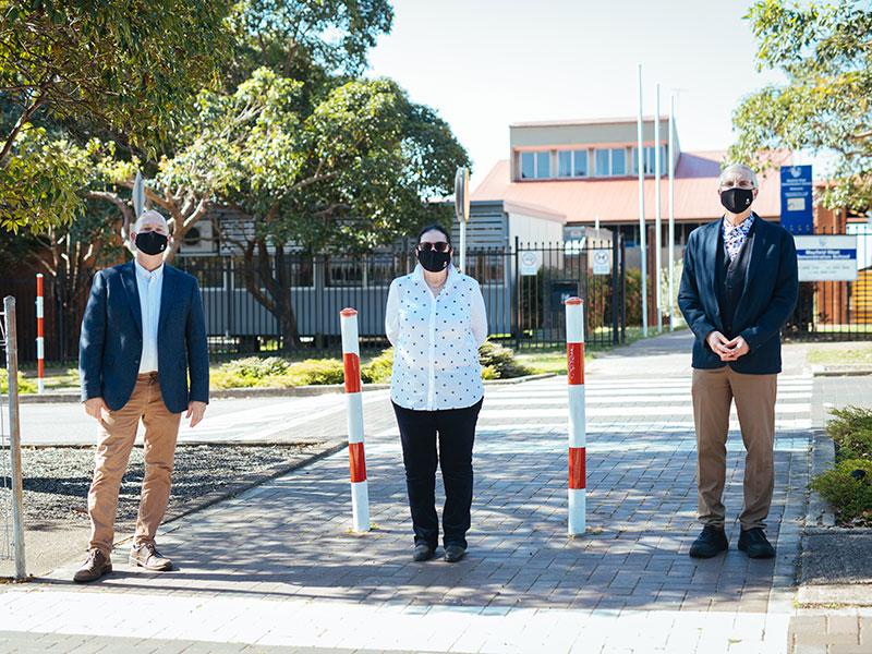 Left to right: Associate Professor Scott Imig, Dr Maura Sellers and Professor John Fischetti stand wearing masks