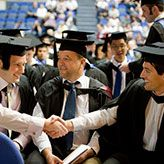 Group of male gradduates in cap and gown shaking hands