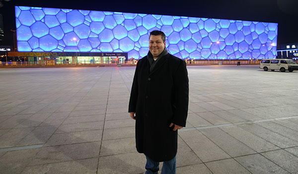 UON graduate Mark Arkinstall in front of the blue 'Watercube' in Beijing