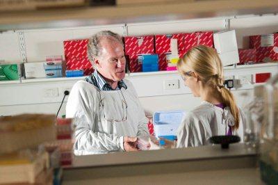 Professor Rodney Scott speaks to a colleague in the laboratory