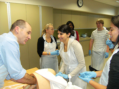Students in the skills lab practice obstetrics with a manikin.