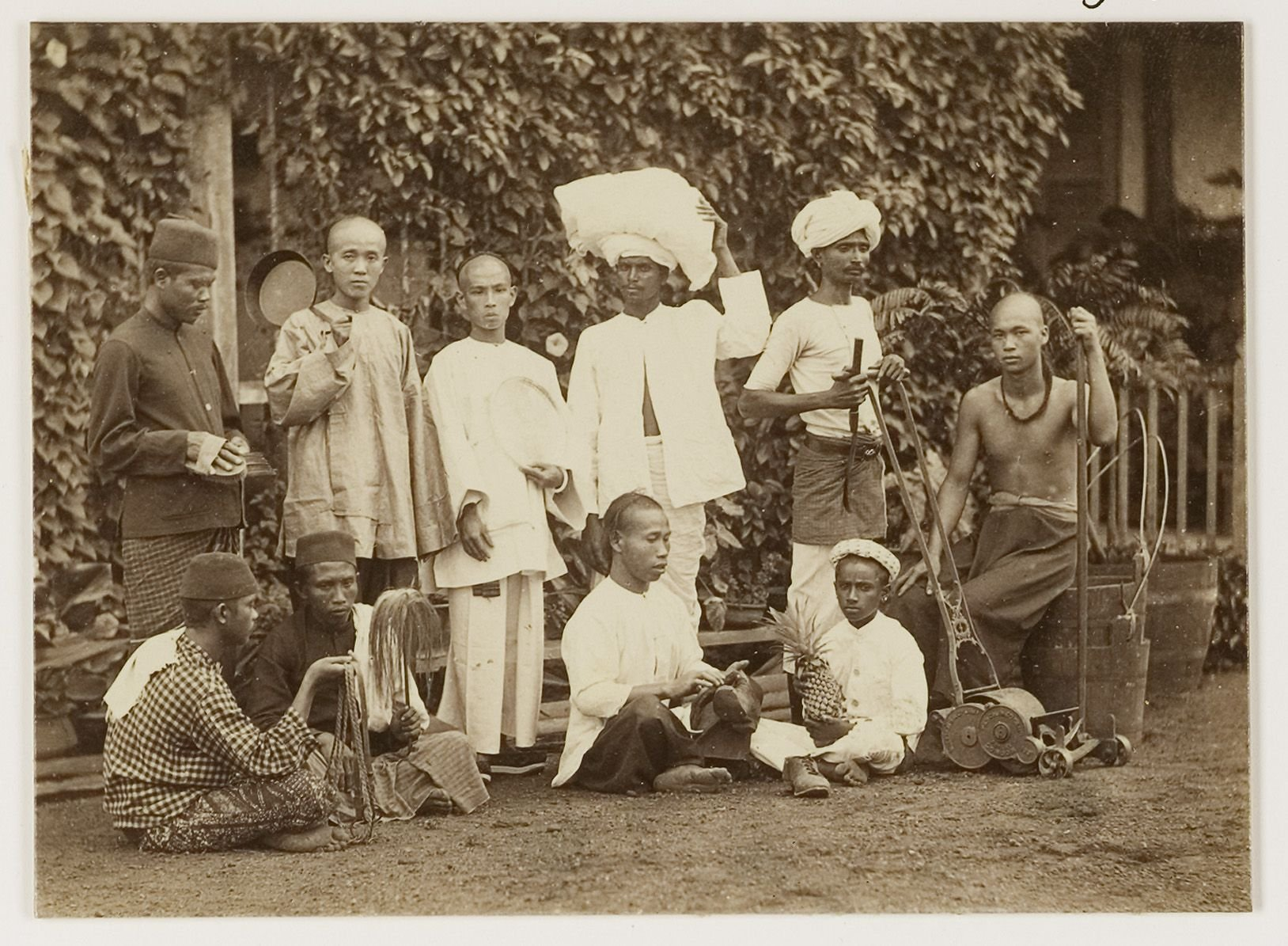 Ten domestic workers of various ethnic origins, each with an object related to their job, Singapore, circa 1900. University of Leiden, Royal Netherlands Institute of Southeast Asian and Caribbean Studies, 29190