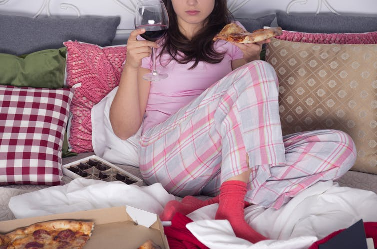 Woman sitting on the couch with glass of red wine