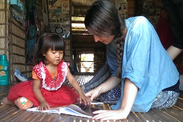 Kelsie helping a child in Cambodia