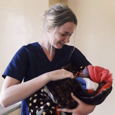 Kate Tolhurst holding a baby she helped deliver in Africa