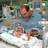 Professor Roger Smith with a baby in an incubator