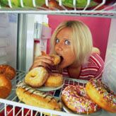 Girl with head in fridge eating donuts